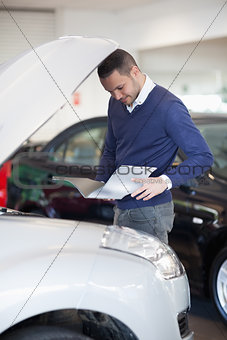 Man reading a file while looking at the engine