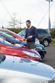 Man looking at a car while holding a file