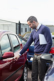 Man looking at a car door while opening it