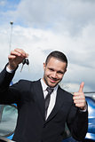 Man holding car keys while raising his thumb