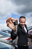 happy dealer holding car keys by his fingertips