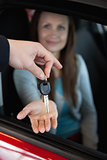 Dealer holding car keys by his fingertips