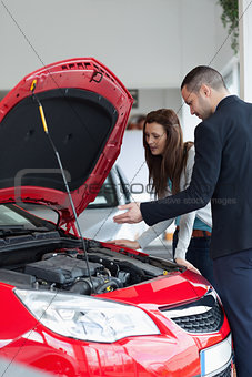 Salesman showing the car engine