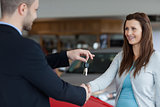 Man giving car keys while shaking hand of a woman