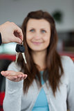 Happy brunette receiving car keys