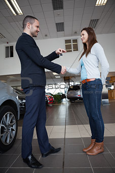 Salesman giving car keys while shaking hand of a client