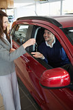 Businesswoman giving car keys to a customer