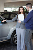 Woman showing a car to a client