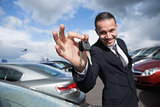 Happy dealer holding car keys