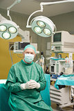 Smiling surgeon sitting while joining his hands together