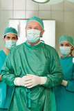 Surgeon joining his hand with interns behind him