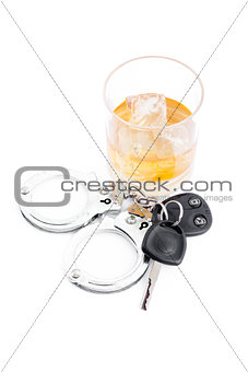 Car key next to a whiskey and a handcuff