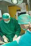 Surgeon holding scissors while operating