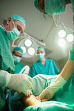 Team of surgeons using scalpel to open a patient
