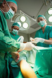 Team of surgeons operating the arm of a patient