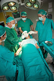 Surgeon working on the arm of a patient with a team of surgeons