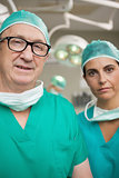 Surgeon with glasses on and a colleague