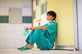 Thinking surgeon sitting on the floor