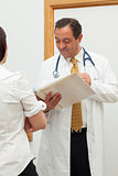 Doctor looking into a file while talking to a woman
