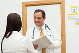 Smiling doctor holding a file while talking to a woman