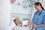 Nurse smiling to a patient while touching her hand