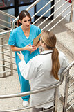 Woman nurse and doctor talking in a stairwell