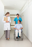 Nurse pushing a patient in a wheelchair while talking to a docto