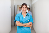 Smiling nurse folding her arms while standing