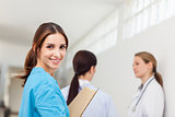 Smiling nurse  while standing in a hallway with a patient and a