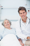 Doctor and patient on the bed looking at camera