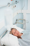 Woman lying on a medical bed while closing her eyes