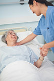 Patient smiling to a nurse while holding her hand