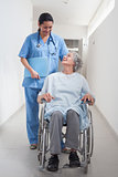 Elderly patient in a wheelchair looking at a nurse