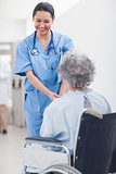 Nurse smiling while holding the hands of a patient