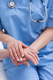 Close up of a nurse holding hand of a patient