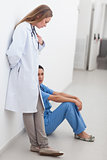 Doctor standing next to a nurse sitting on the floor