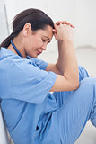 Nurse sitting on the floor with her head on her hands