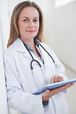 Doctor looking at camera while holding a tablet computer