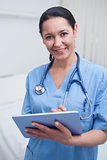 Nurse looking at camera while holding an ebook