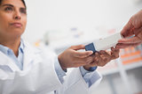 Close up of a pharmacist giving a box to someone