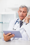 Doctor holding a tablet computer while calling