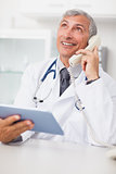 Doctor calling while holding a tablet computer