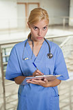 Serious nurse writing on a clipboard