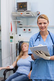Nurse holding a clipboard while looking at camera
