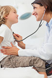 Smiling doctor auscultating a child with a stethoscope