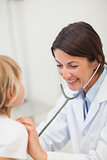 Smiling doctor auscultating a child