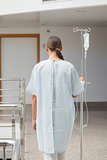 Rear view of a female patient holding a drip stand