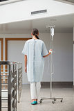 Rear view of a patient holding a drip stand