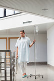 Female patient walking while holding a drip stand