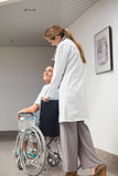 Patient sitting on a wheelchair looking at a doctor